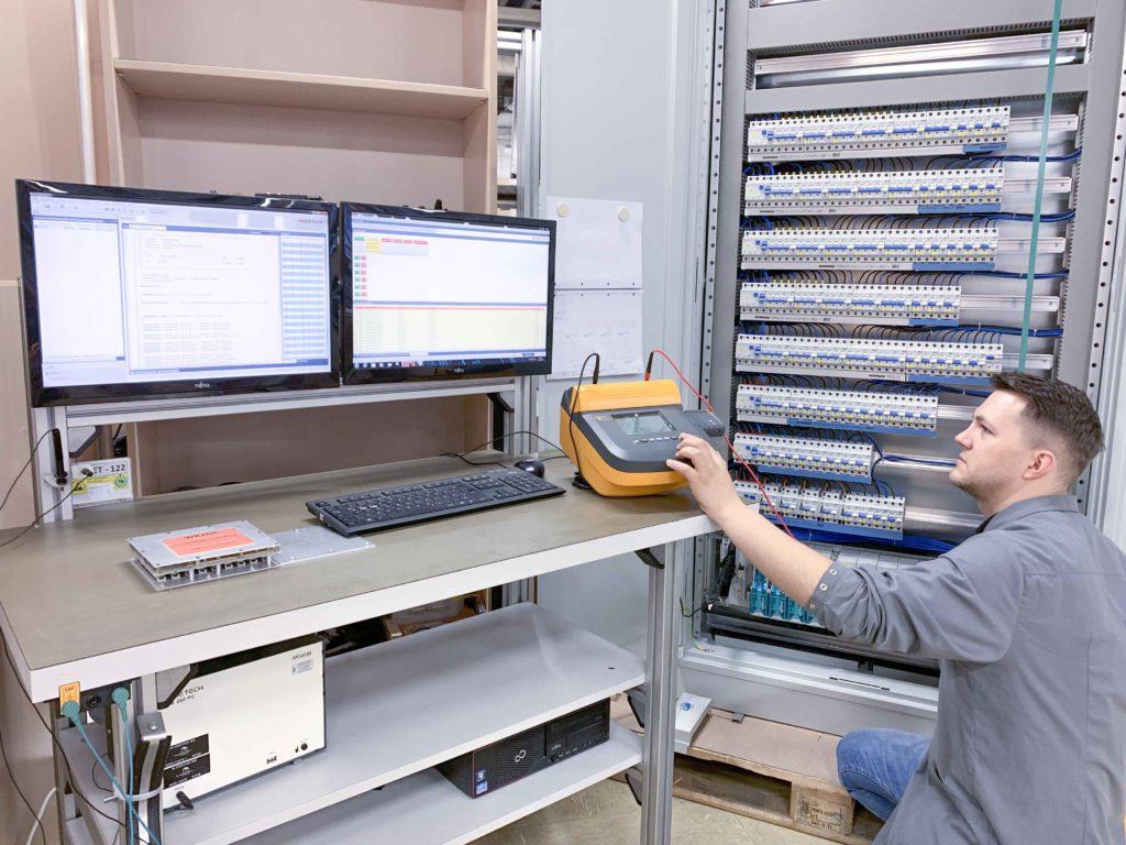 Mitarbeiter beim programmieren eines Schaltschrankes