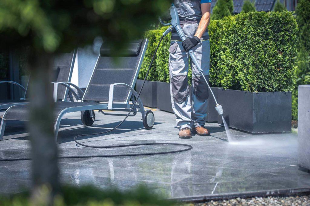 Arbeiter, der Terrasse mit Wasserstrahler reinigt
