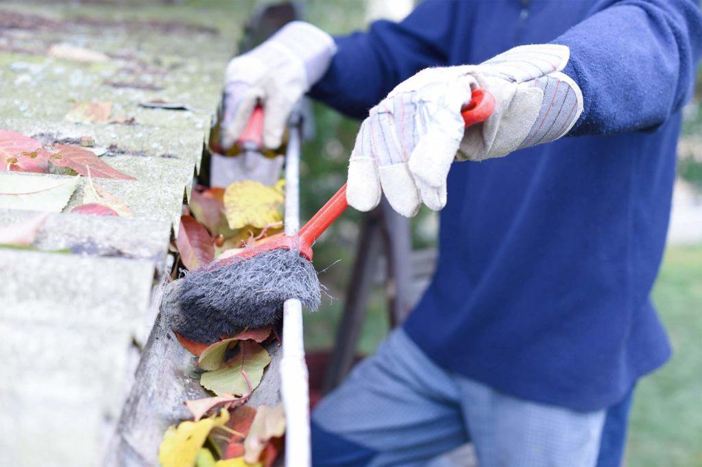 Arbeiter, der das Laub aus einer Dachrinne beseitigt