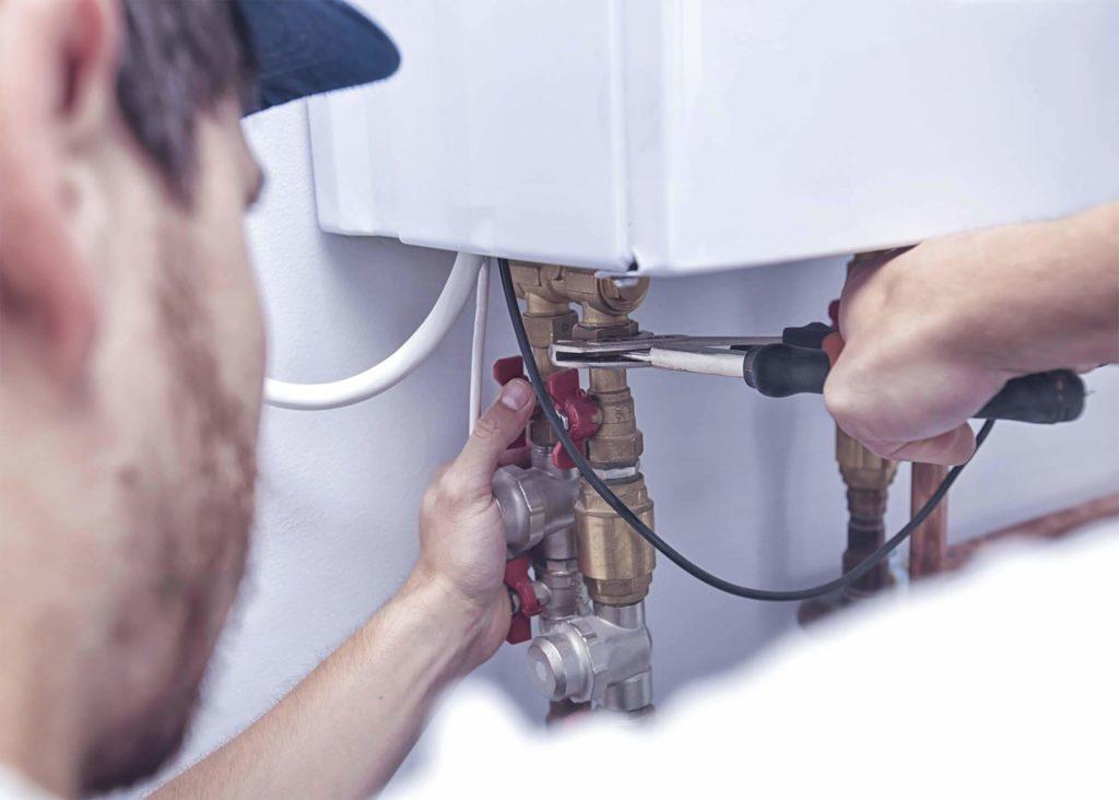 Arbeiter, der einen Boiler installiert