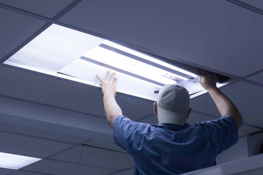 Arbeiter, der Neonröhren wechselt