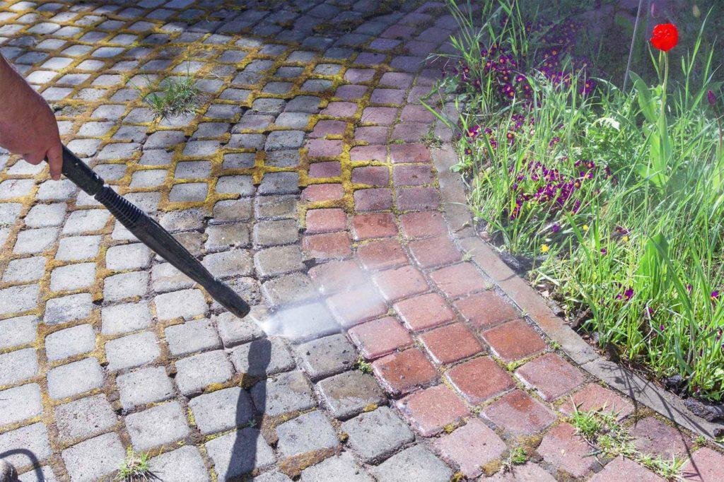 Arbeiter, der den Boden mit einem Wasserstrahler reinigt