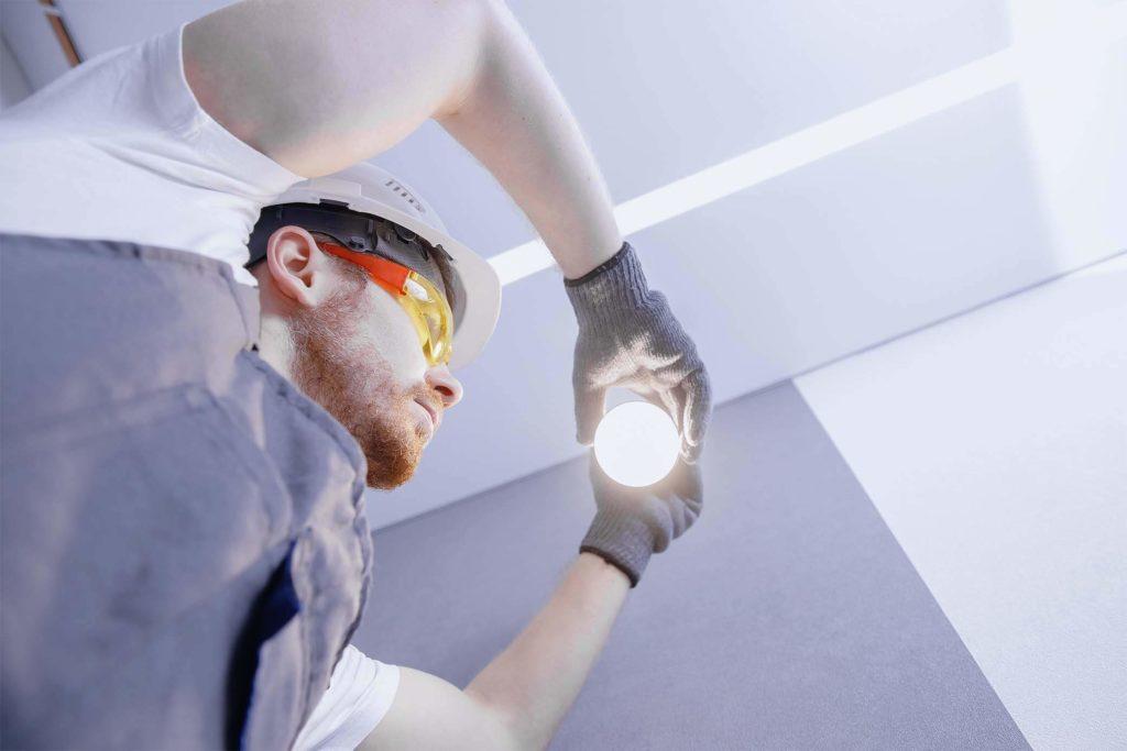 Arbeiter, der eine Glühbirne wechselt
