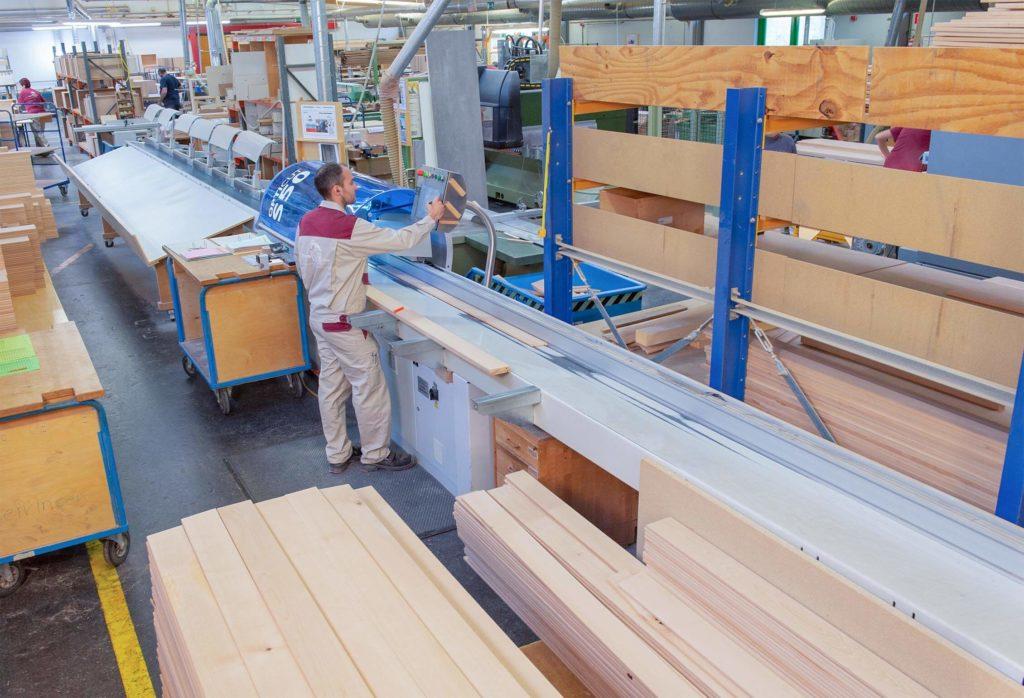 Mitarbeiter, der an automatisierter Kappsäge Holz zuschneidet