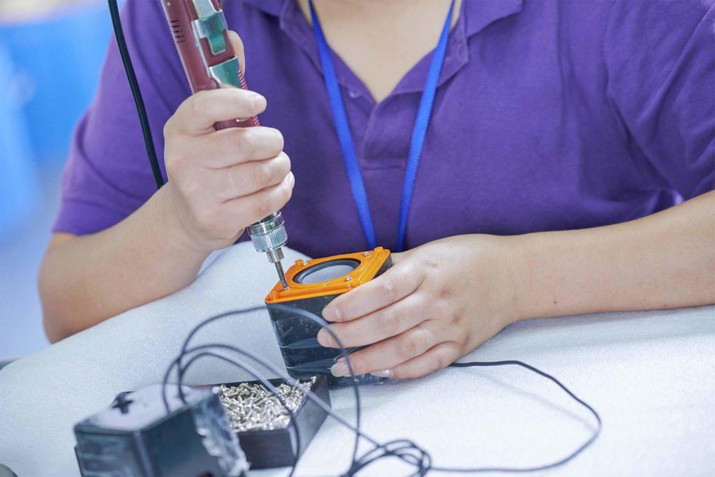 Arbeiterin baut einen Lautsprecher zusammen