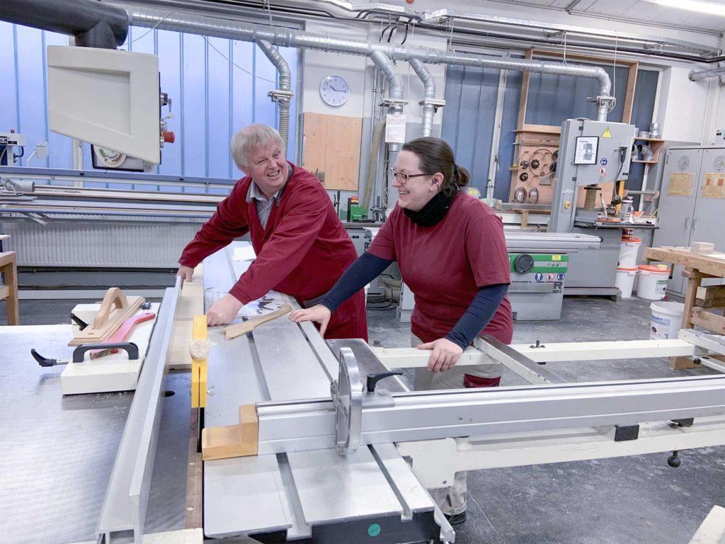 Zwei Mitarbeiter, die Holz zurecht schneiden
