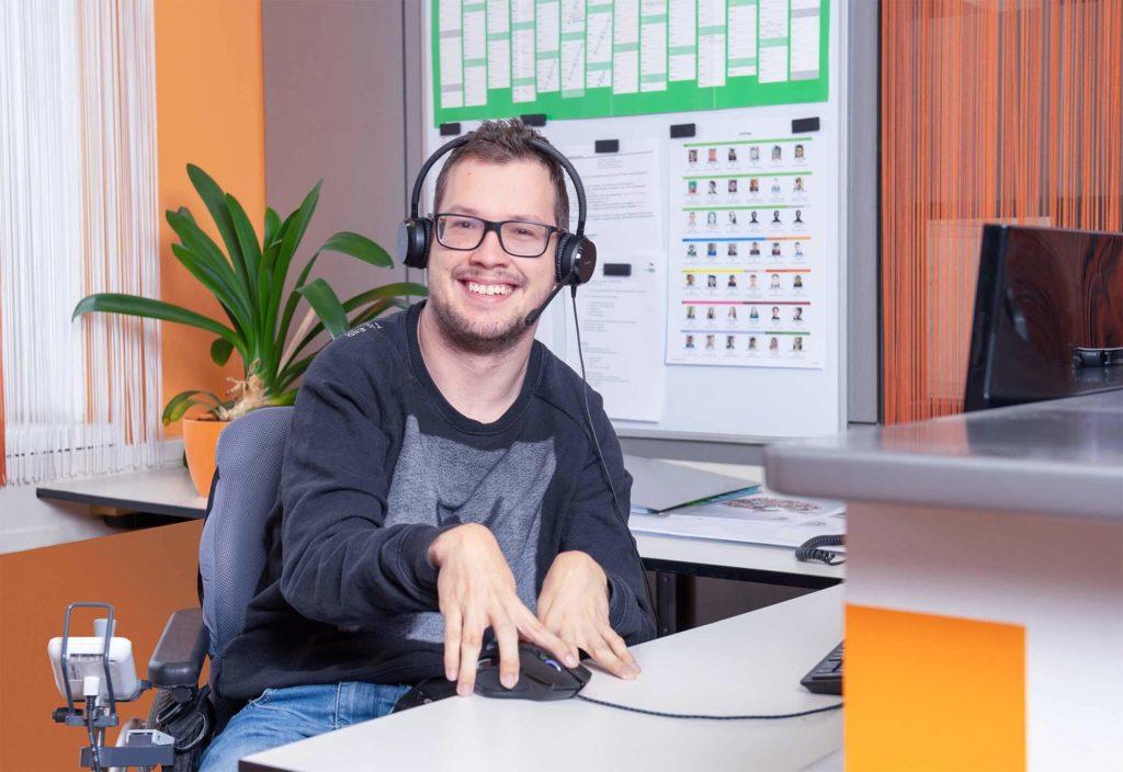 Mitarbeiter, der vor dem Computer mit einem Headset arbeitet