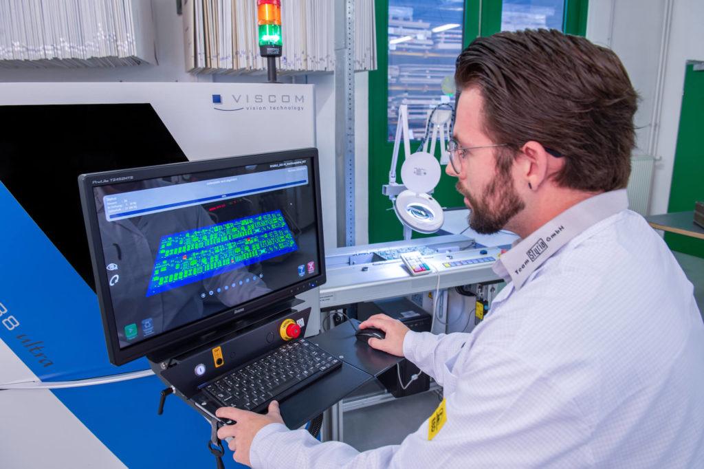 Ein Mitarbeiter der E-Technik-Abteilung bedient einen Computer an der SMD-Produktionslinie