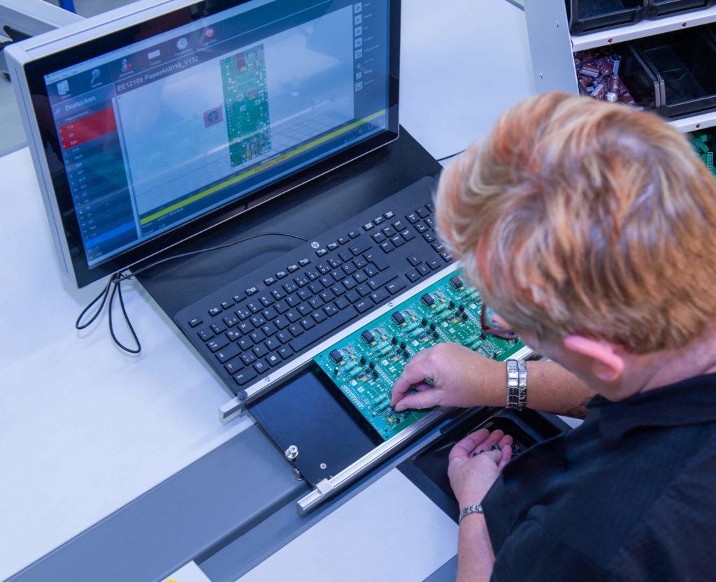 Eine Mitarbeiterin der E-Technik-Abteilung platziert händisch Bauteile auf einer Leiterplatte