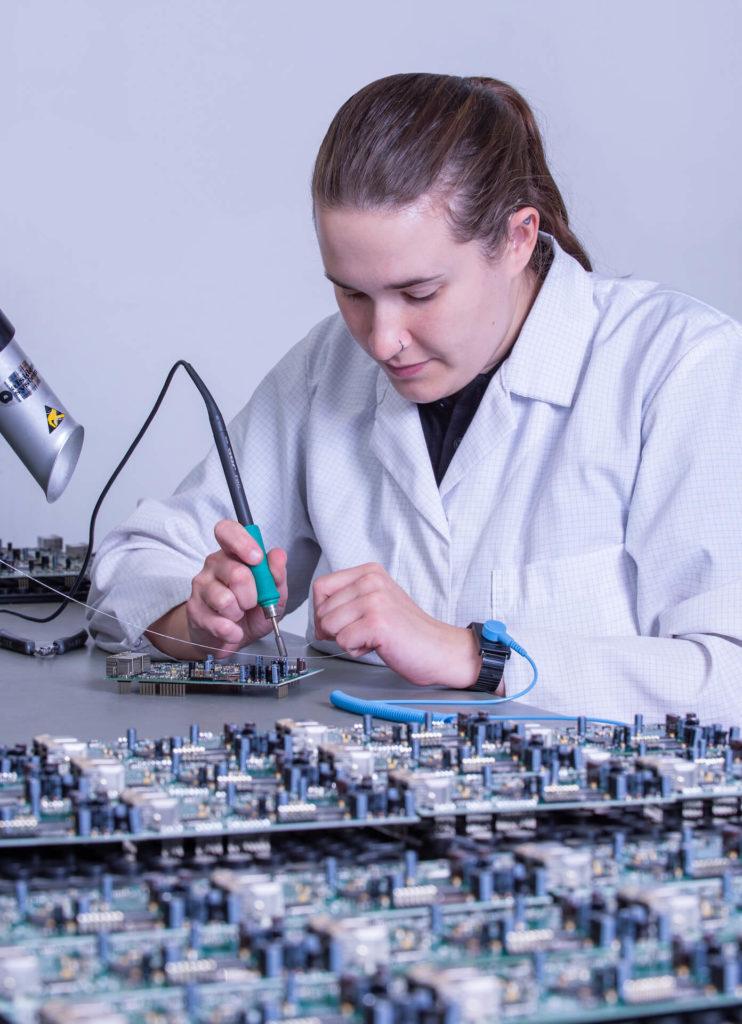 Eine Mitarbeiterin der E-Technik-Abteilung bearbeitet händisch Bauteile auf einer Leiterplatte
