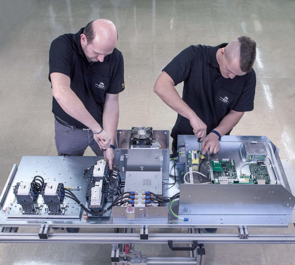 Zwei Mitarbeiter der E-Technik-Abteilung fertigen einen Schaltschrank bzw. einen Verteiler