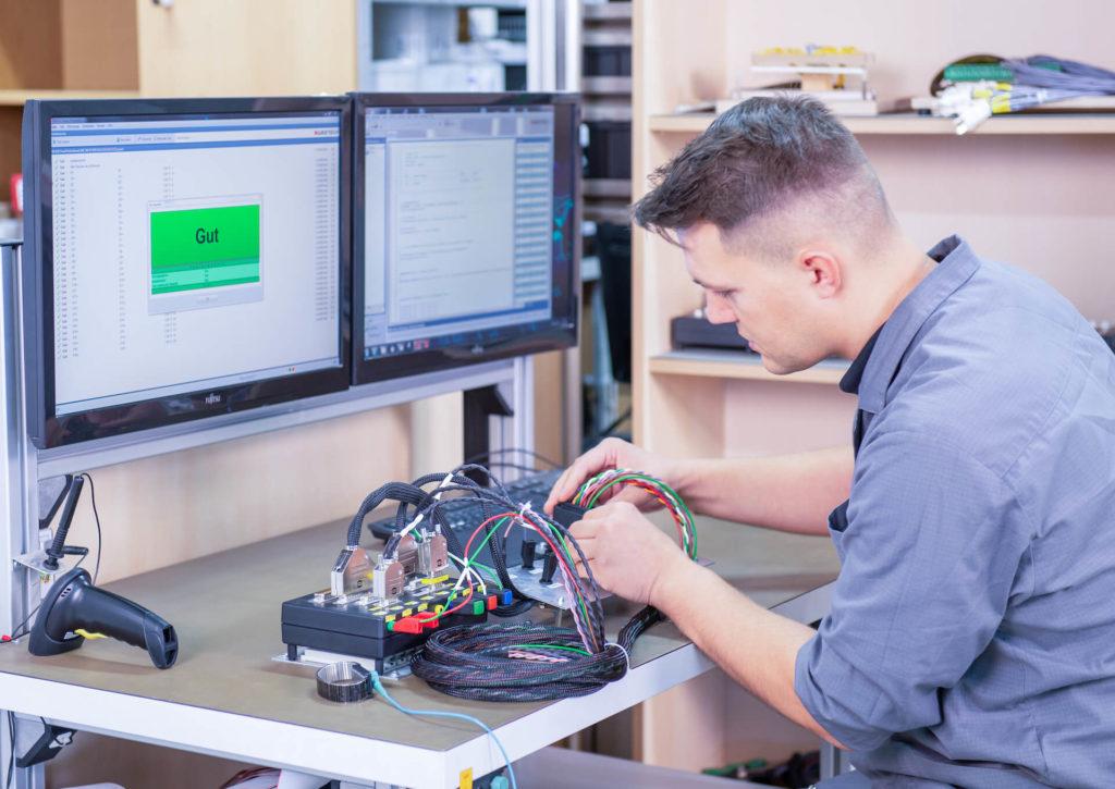 Ein Mitarbeiter der E-Technik-Abteilung überprüft ein elektronisches Bauteil, die Prüfstation ist grün und zeigt gut an
