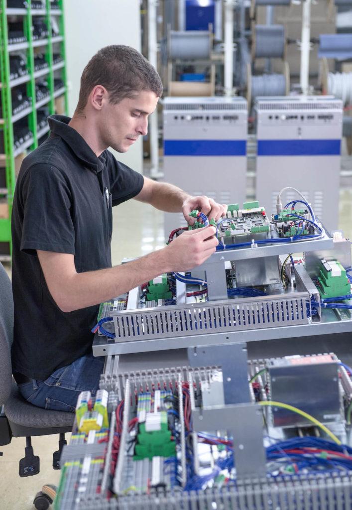 Ein Mitarbeiter der E-Technik-Abteilung verlegt Kabel in einem Schaltschrank bzw. Verteiler